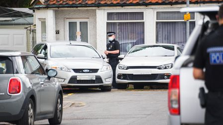 A Police officer stands outside a property on Milton Avenue in King's Lynn