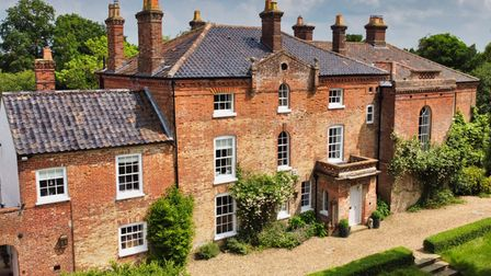 Aerial photograph of huge 18th century rectory with shingled drive behind boxes hedges