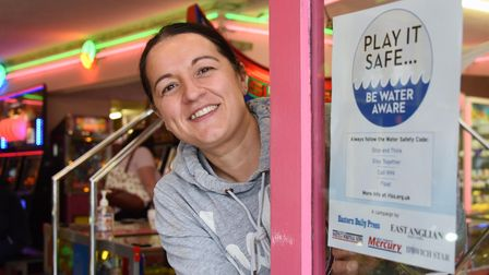 Grays Amusements cashier Francesca Nicholls puts up the Eastern Daily Press Water Safety awareness p