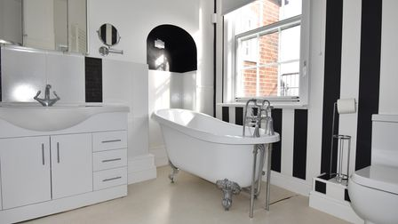 Period-style bathroom with black and white striped wall, an arched alcove and free-standing roll-top bath
