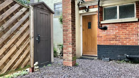Wooden door to brick-built apartment building with shingled driveway and small storage shed