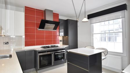 Sleek contemporary kitchen with bright glossy red tiling, integrated appliances and modern angled extractor hood