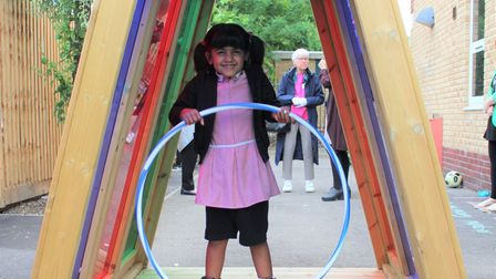 A pupil explores the colourful tunnel in the deaf alternative resource provision (ARP) outdoor learning space.