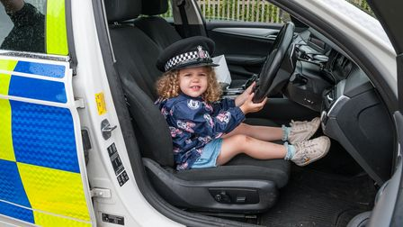 A little girl at the wheel of a police car in Rayne, Essex