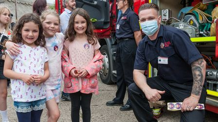 Three girls and a fire service officer wearing a mask.