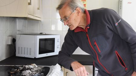 Mike Gibb, management committee treasurer, with the ashes of a cooker faults log book, set on fire i