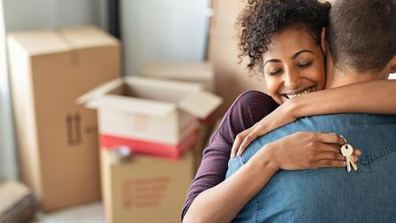 Young african woman holding home keys while hugging boyfriend in their new apartment after buying re