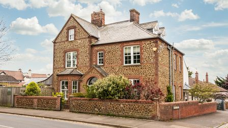 Angled view of large brick and flint Victorian-era home surrounded by low brick wall