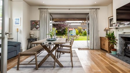 Bright modern dining room with bench seating in front of bi fold doors opening out on to terrace