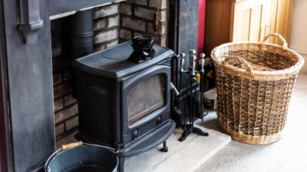 Close up of cast iron woodburner set into a brick built hearth with wicker log basket beside it