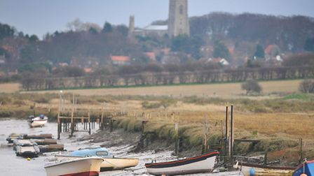 Boats tied up during low tide at Morston Quay with Blakeney church in the background. PHOTO: ANTONY