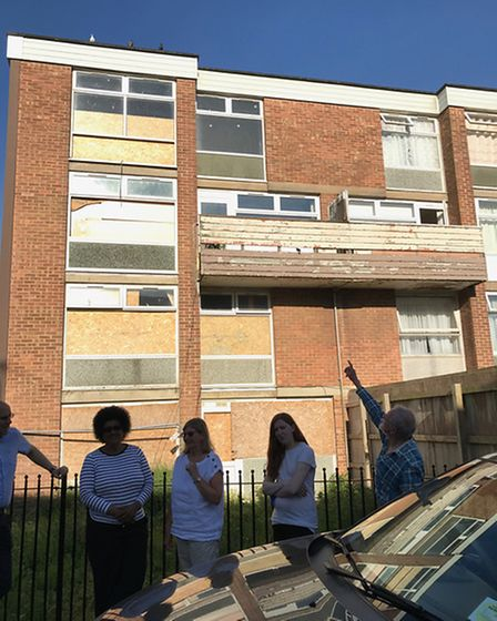 BASSA members outside boarded up flats where pigeons are said to be getting into.