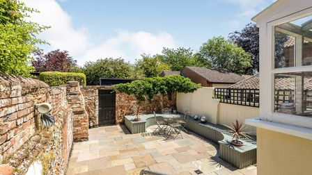 Large walled garden with flagstone patio, curved timber seating area and trellis