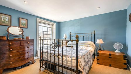Bedroom with teal painted walls, wrought iron double bed, large wooden dresser and sash window