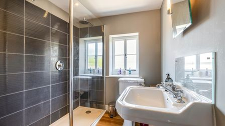 Modern shower room with large walk-in shower, white toilet, white sink with mixer taps