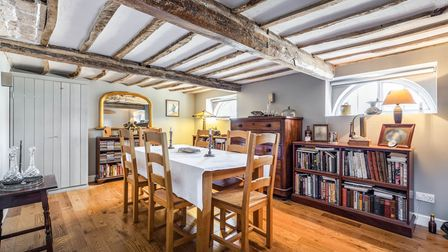 Large basement-level dining room with chair and tables in the centre, wooden floors and timber beams on ceiling
