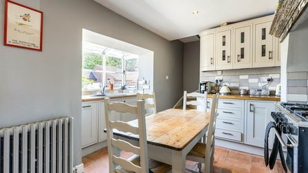Country-style kitchen with blue base and wall units, kitchen table to seat four and box bay window