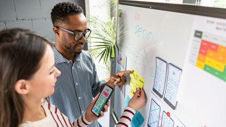 Designers drawing website ideas on a white board