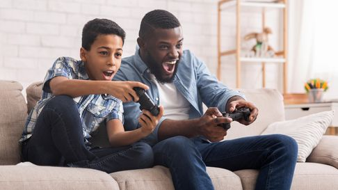 Leisure With Dad. Cheerful Black Father And Son Competing With Each Other In Video Games, Using Joys