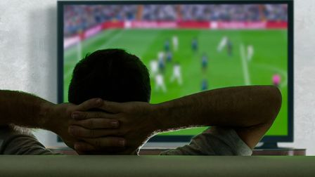 view from behind of young and happy soccer fan man watching European football game on big screen tel