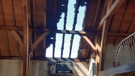 A wooden structure with a burnt-out roof after a fire in Bardfield, Essex