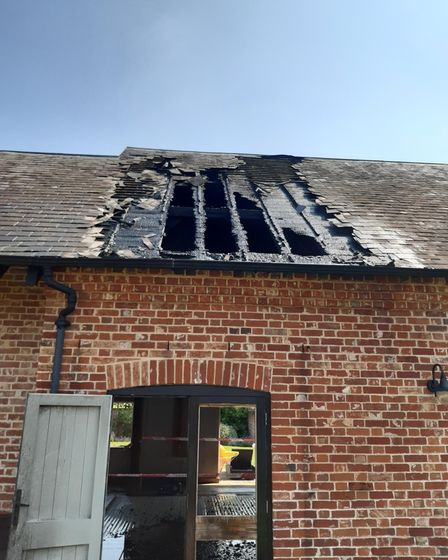 A brick building with a hole in the roof after a fire in Bardfield, Essex
