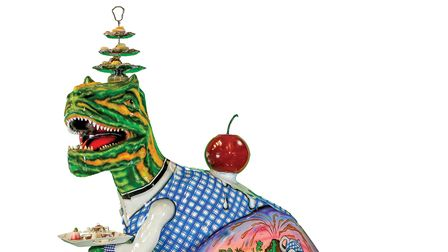 A statue of a dinosaur with a cherry on its back, a tea stand on its head and balancing a plate on its arm