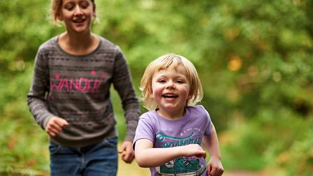 Two young girls running along a RSPB nature reserve path