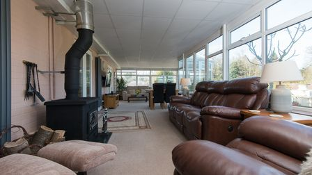 Huge light-filled conservatory with dining table, several sofas and wide panoramic windows