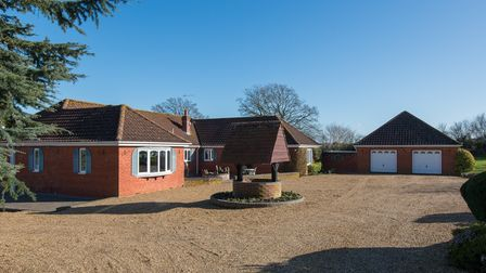 U-shaped brick-built bungalow with gravel driveway, double garage and turning circle with well