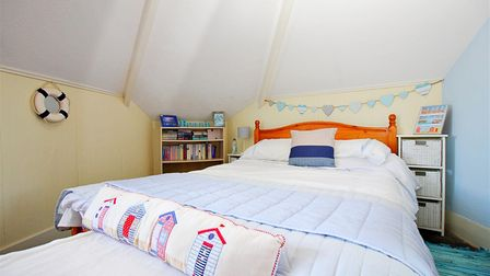 Beach themed double bedroom with vaulted ceilings, pine bed, life buoy mirror