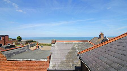 View from second storey window overlooking roof tops towards Mundesley beach