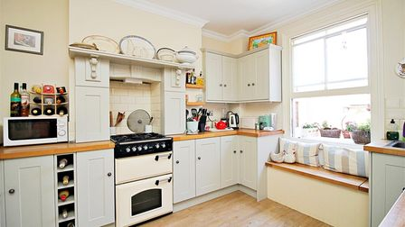 Beige coloured fitted Shaker-style kitchen with wooden floor, wooden window seat, wine rack and cupboards