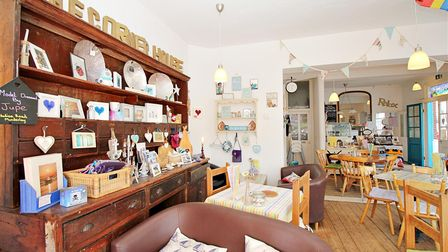 Shabby chic style cafe with pine tables and chairs, dresser, bunting and wooden floors
