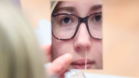 Erin Horn looking in a mirror while taking a Lateral Flow Test as children arrive at Outwood Academy