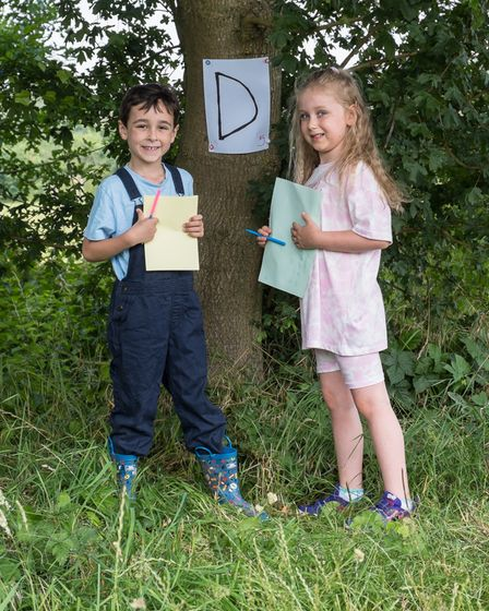 Two children under a tree with the letter D pinned up, during a treasure hunt in Great Dunmow, Essex