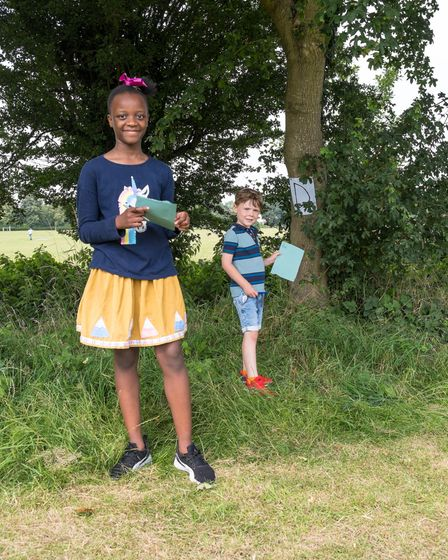Two children searching for letters pinned to trees during a treasure hunt in Great Dunmow, Essex