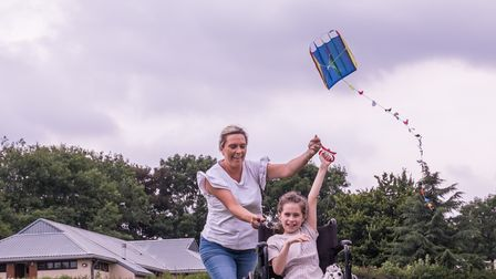 A woman and a child in a wheelchair having fun flying a kite at Great Dunmow's Teddy Bears' Picnic, Essex