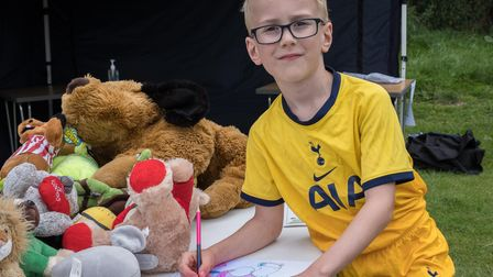 Child colouring in, surrounded by teddy bears during a Teddy Bears' Picnic in Great Dunmow, Essex