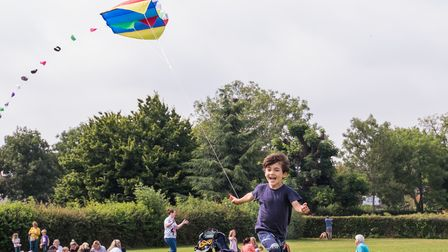 A child smiling and running, a kit in the background, at Great Dunmow's Teddy Bears' Picnic, Essex