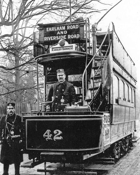 A black and white picture of a tram conductor standing on a tram.