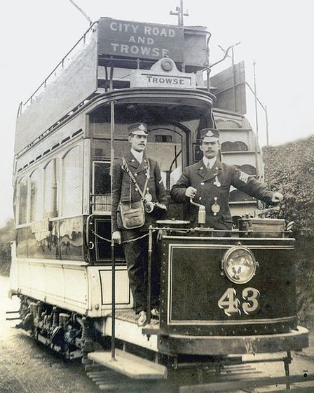 Two tram conductors stand on a tram.