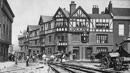 A group of men lay tram tracks in front of the Maids Head.
