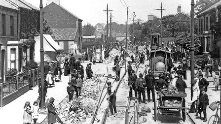 Workmen lay tram tracks on Magdalen Road. Groups of people stand watching the work.