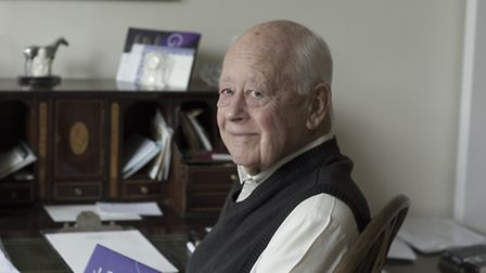 Charles Handy in his office in Norfolk with a copy of his book The Second Curve