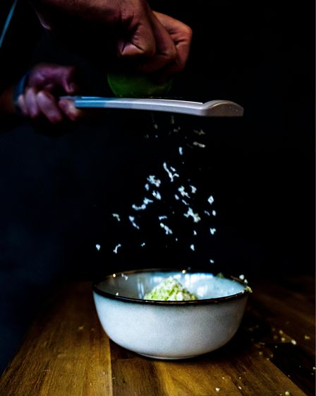 Grating frozen apple over celery and rosemary compressed Granny Smith apple, elderflower syrup and edible flowers