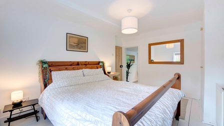 White double bedroom with pine sleigh bed, bedside table with lamp, mirror, door open to landing