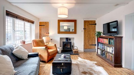 Large reception room with wooden floors, huge windows, wooden bookcase with TV on top, trunk style coffee table