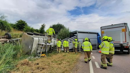 Firefighters inspect an overturned trailer and Land Rover Defender on the A120 in Essex