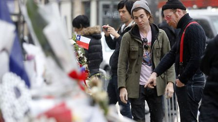 Members of the band Eagles of Death Metal, Jesse Hughes, right, and Julian Dorio pay their respects